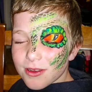A little boy with a snake eye and green scales painted on the left side of his face. Click to view at full size.