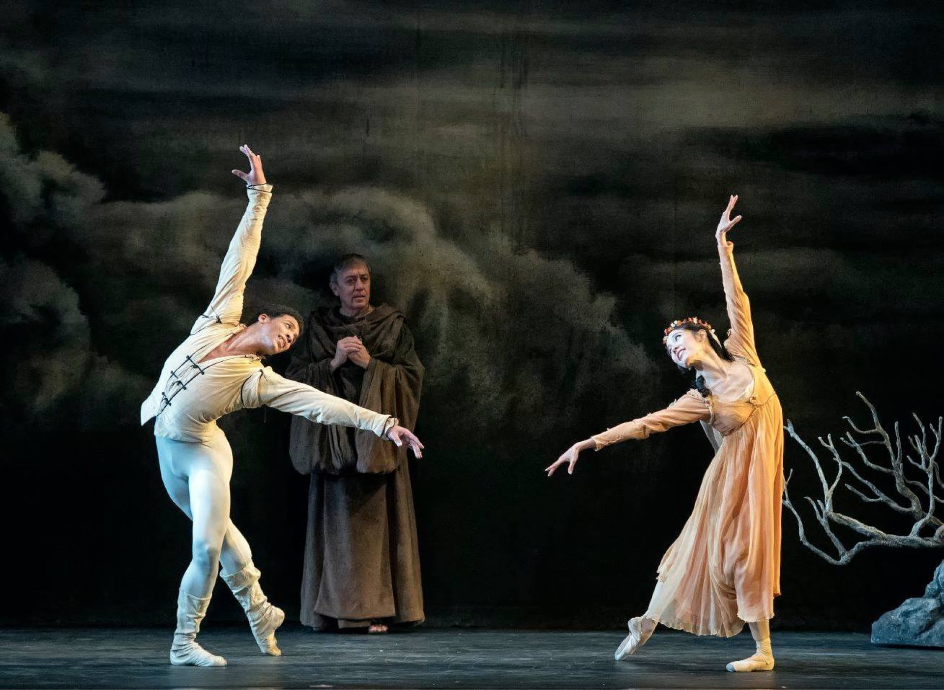 Dancer in white and ballerina in peach share longing look in front of anxious friar against dark cloudy sky.