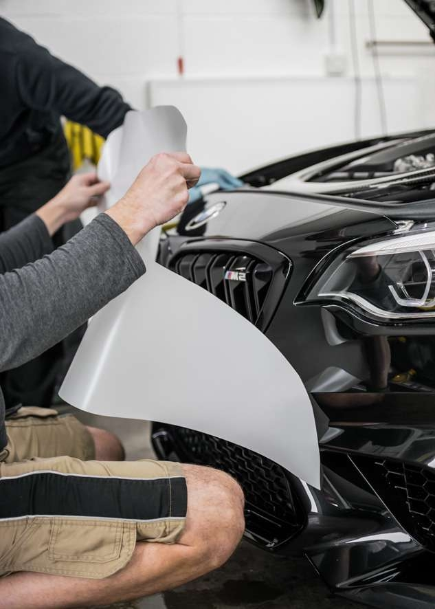 Paint protection film (PPF) being applied to front bumper of black BMW M2C