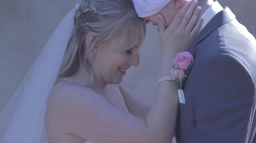 Bride smiling at blindfolded groom