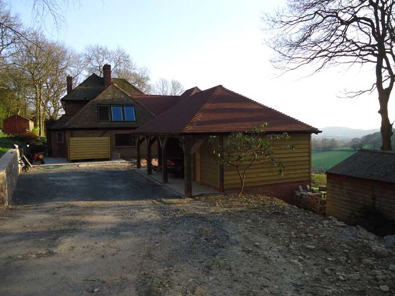 A new timber framed garage with oak pillars and wooden slats, for a client's property overlooking the Malvern Hills