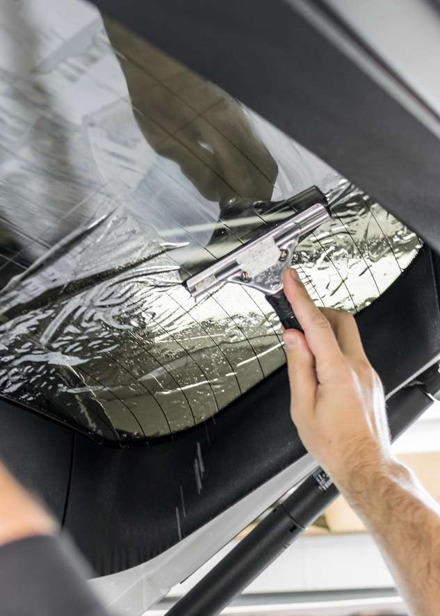 Rear window being tinted using LLumar window tinting film on White BMW X5