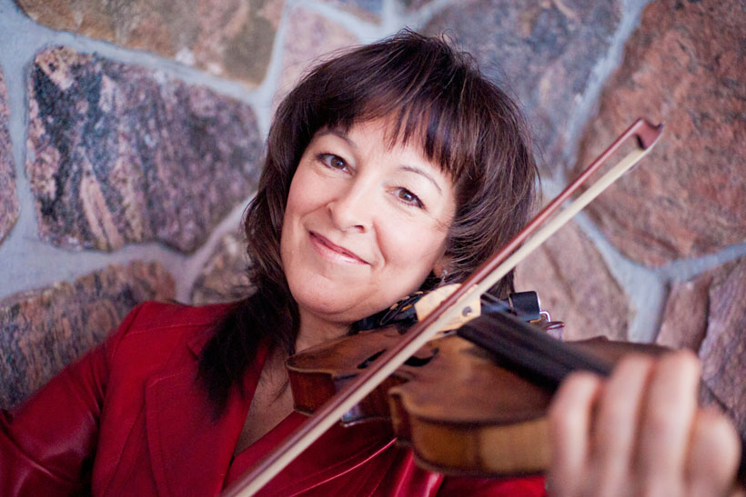 A photo of Cindy Thompson smiling and playing her fiddle.