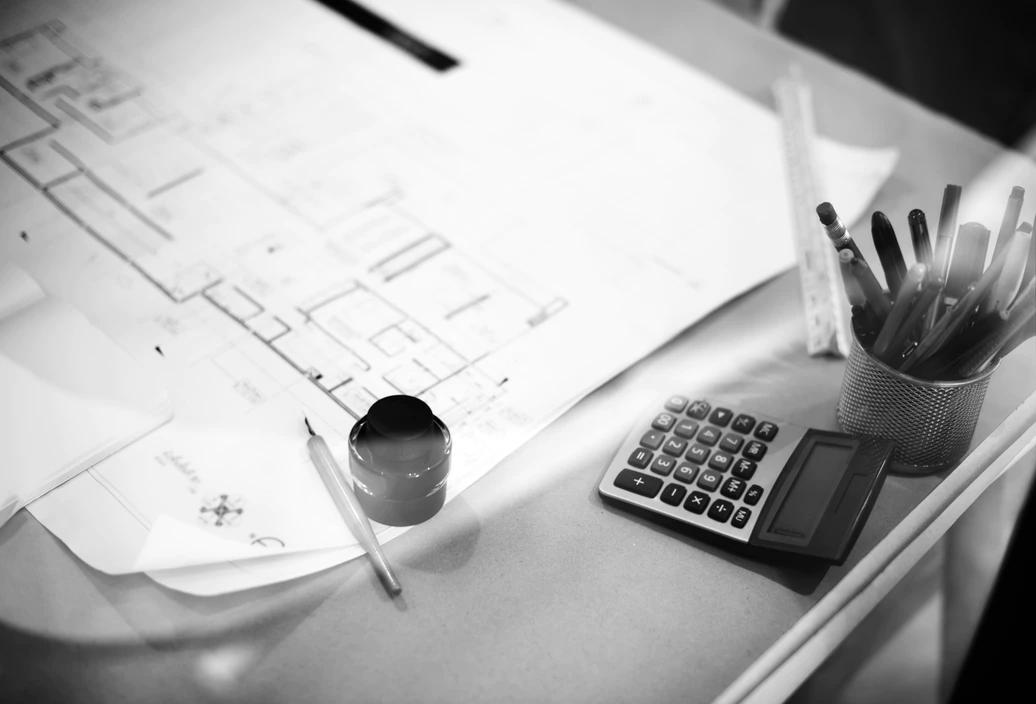 black and white blueprints with ink and pen next to calculator on desk showing roofing calculations