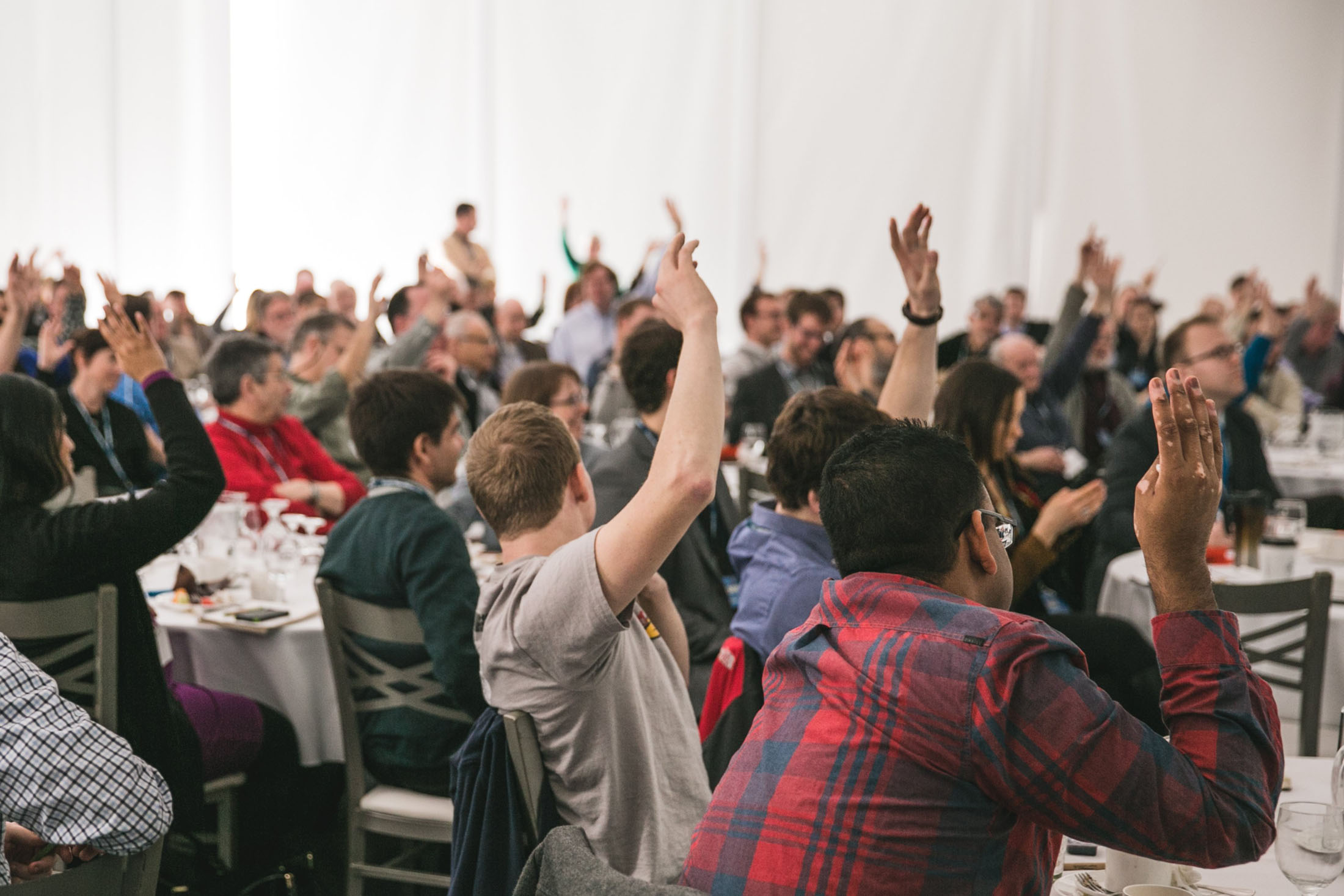 large group of business people dressed in business-casual engaged in an event putting their hands up