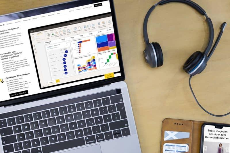 Foto von einem Laptop mit Power BI-Bericht, Handy und Headset