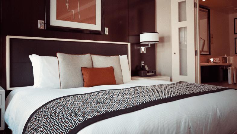 Hotel room bed, cushions, runner, painting, shelving #kpi
