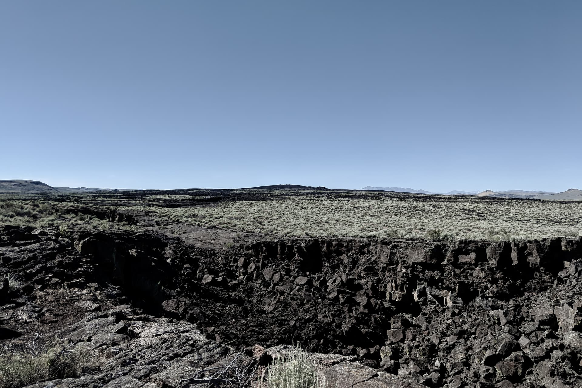 A U-shaped dark basalt boulder field, all that is left of a collapsed lava tube. Beyond it, desert scrubland, and finally distant mountain peaks. In the middle-distance is a low, black hill -- the shield volcano where the lava tube originated.
