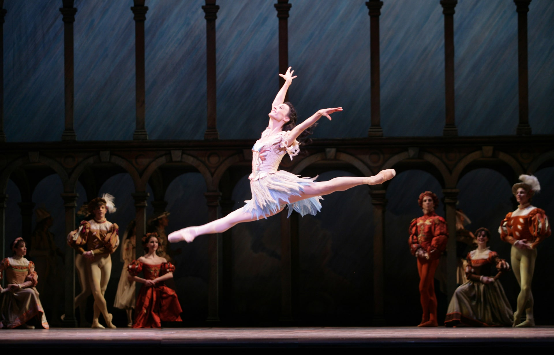 Ballerina in white feathery skirt leaps arms outstretched, watched by courtly dancers in front of arches against painted blue sky.