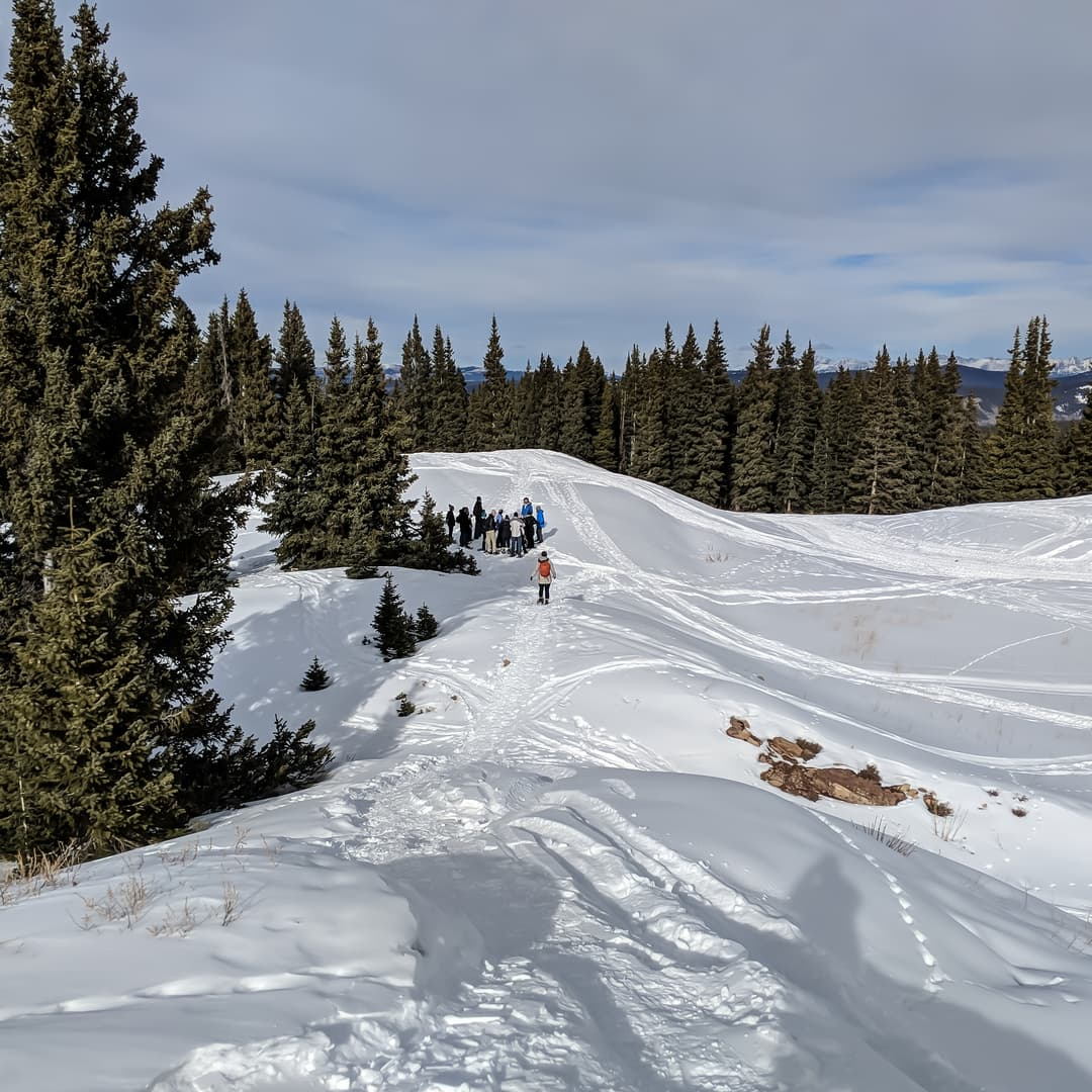 A woman with a bright orange backpack snowshoes towards a distant knot of winter hikers on the summit of Aspen Mountain.