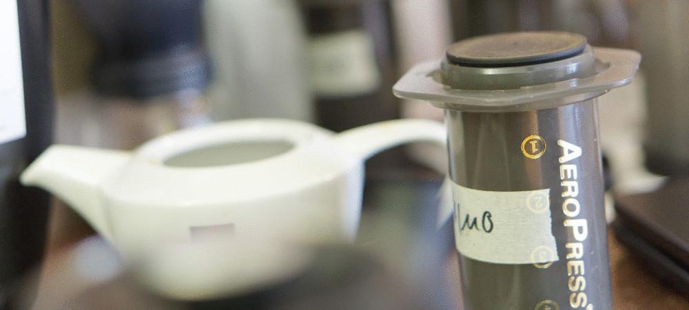 An aeropress coffee maker in front of a tea pot