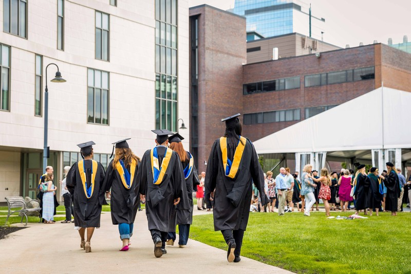 Recently graduated students in their caps and gowns walk toward a reception