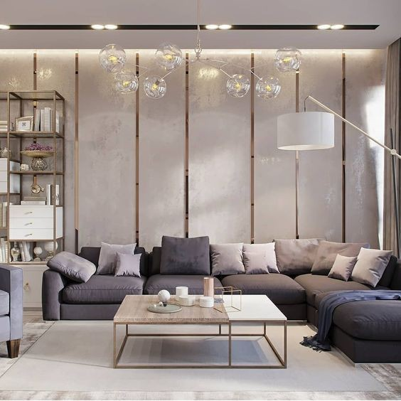 Best interior designers in bangalore - living room interior designs which include marble flooring, wooden false ceiling with wall mounted lights, mosaic wall paintings, L shaped 5 seater leather or fabric sofas with small table or ottoman.