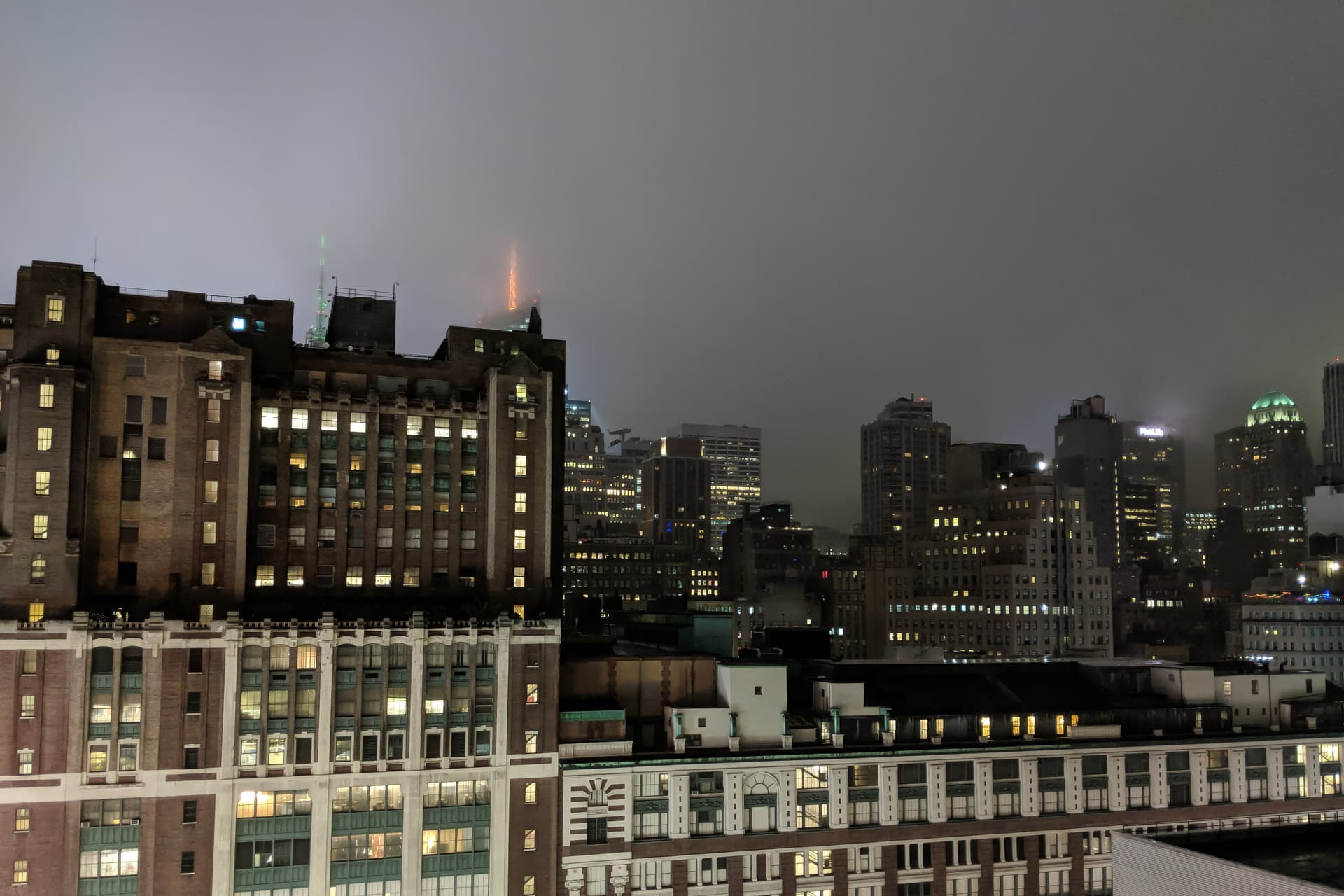 A New York City skyline at night. Low rain clouds hang overhead.