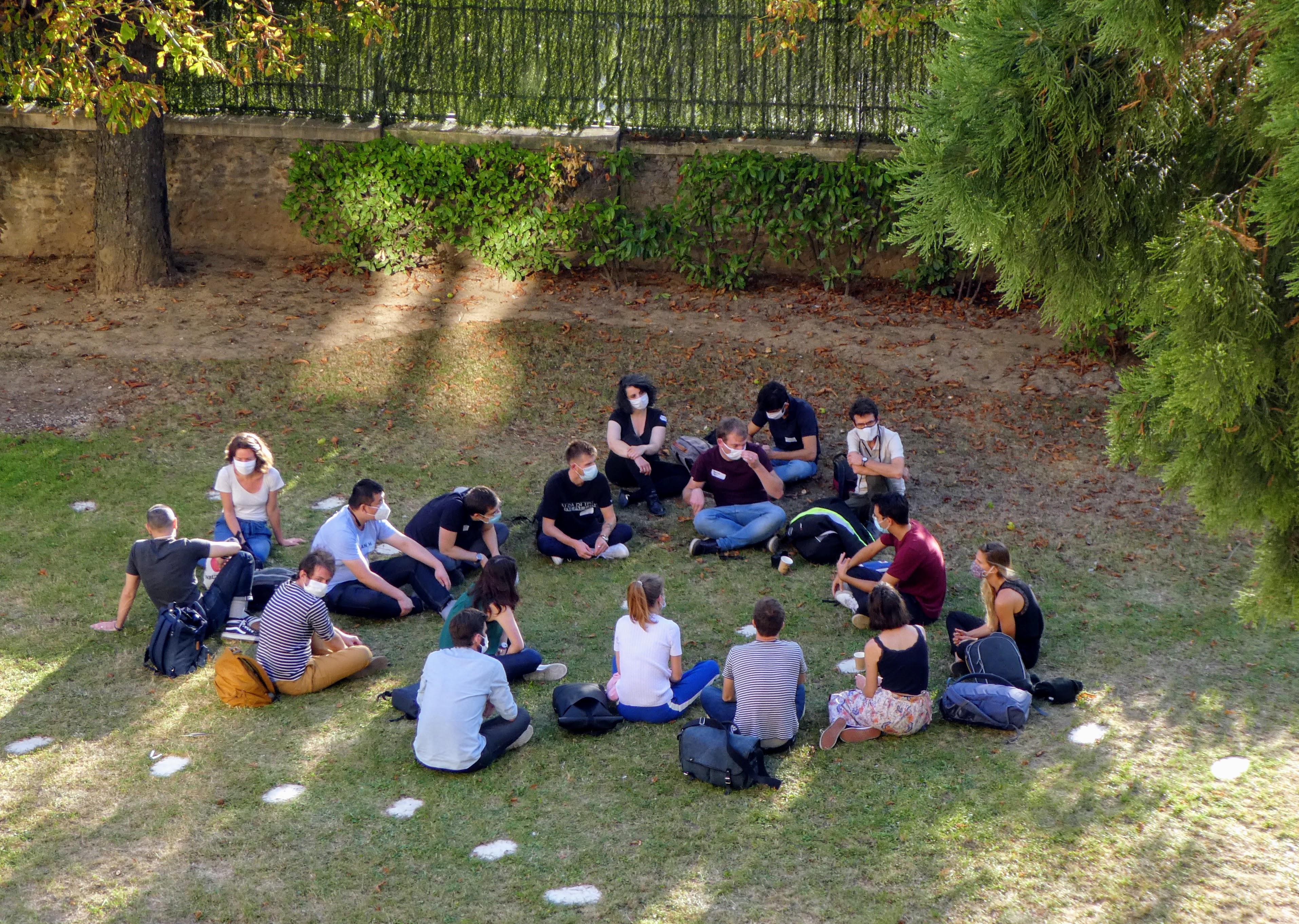 Une vingtaine de personnes sont assises dans l'herbe, en cercle. Elles échangent