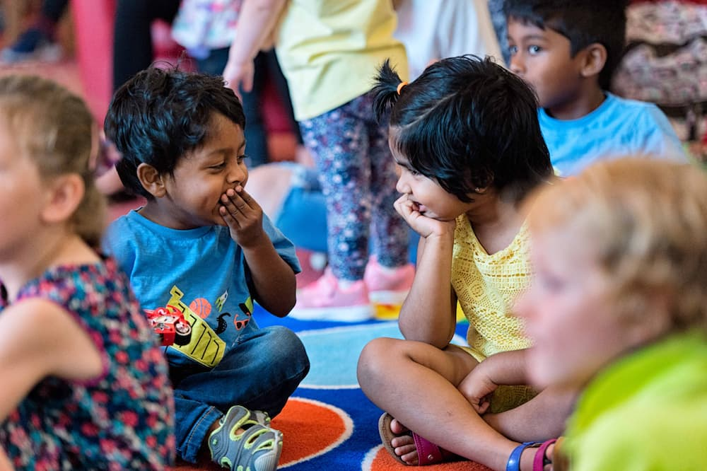 Two young children sitting on a library floor laughing.