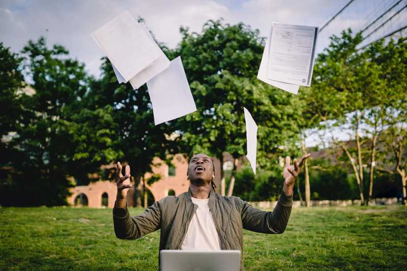 Man throwing files up to the sky