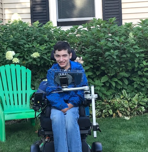 Joe Carr smiling and sitting outside house in wheelchair
