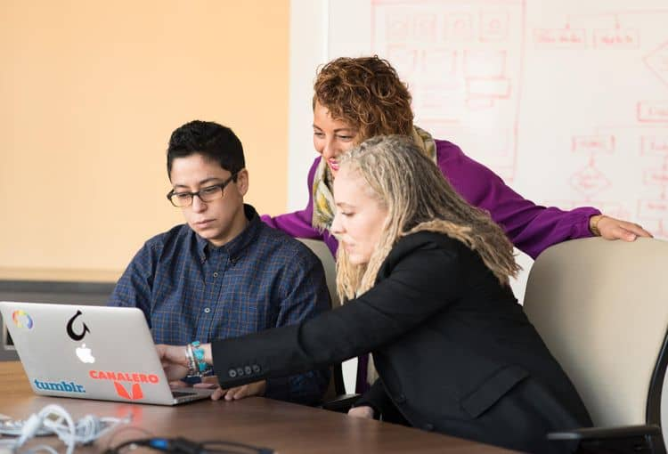 Trainerin mit zwei Teilnehmern an Laptop während eines Workshops