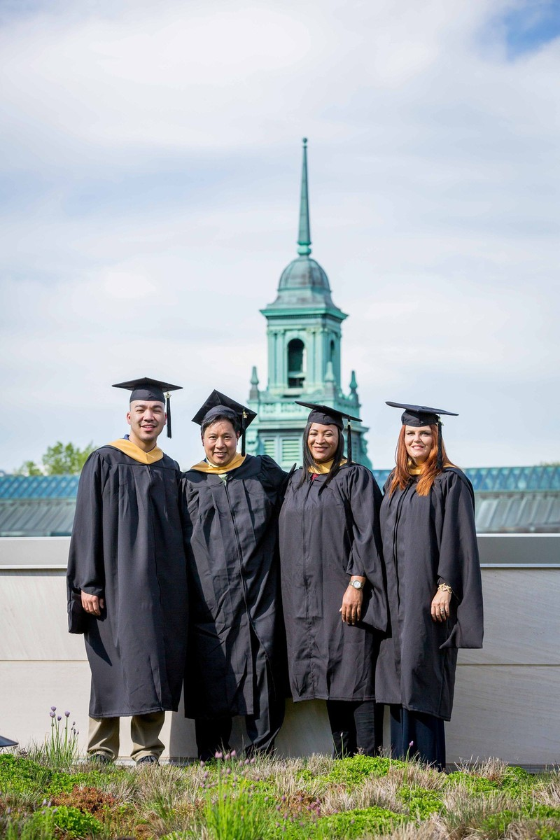 A group on Simmons University graduates posing for a photo with the main building steeple in the background
