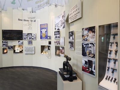 Various photographs are on display, along with glass showcases of book stamps and due date cards. An old book-press machine is on a pedestal. Next to it on a wall, there is a small TV screen with audio handsets.