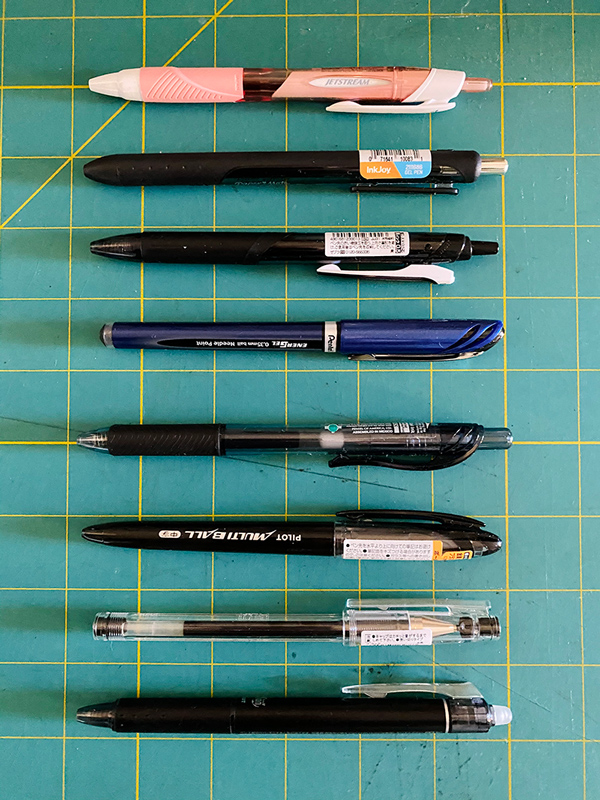 The pens laid out on top of an Olfa cutting mat. Except the first pink pen, which is a ballpoint, all are gel pens.
