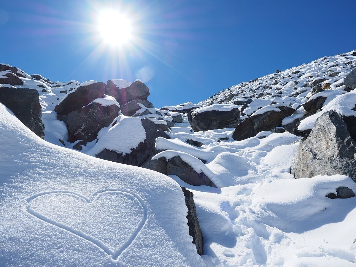 Heart (cardio) in snowy mountain and sun at the top