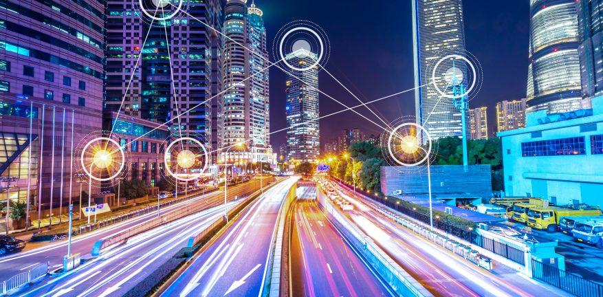 Uma cidade com luzes de tráfego e uns pontos tecnológicos em alguns prédios