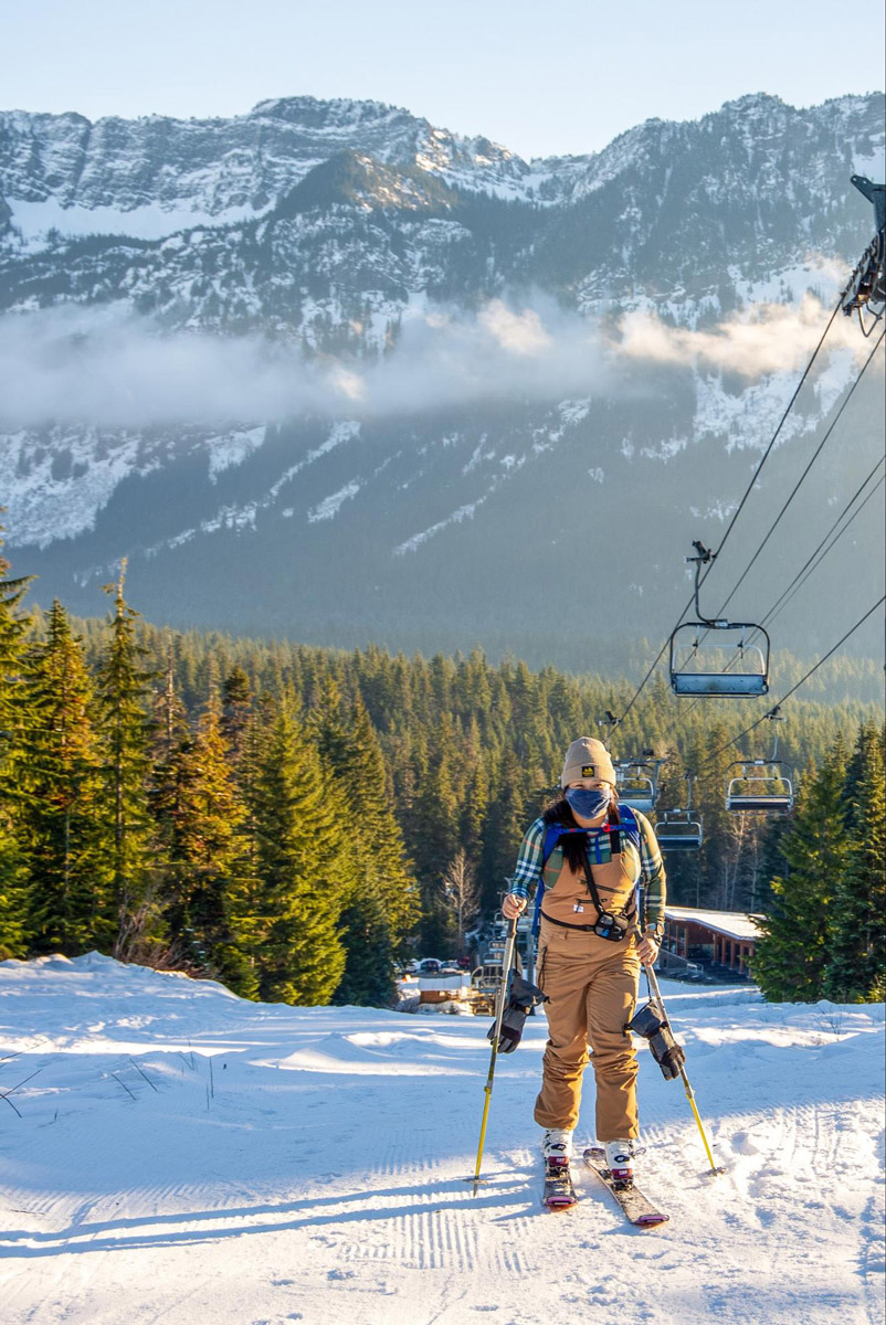 Woman skiing up a snowy slop with a pine forest and snow-capped mountains in the distance. A ski lift is to the right side of the photo