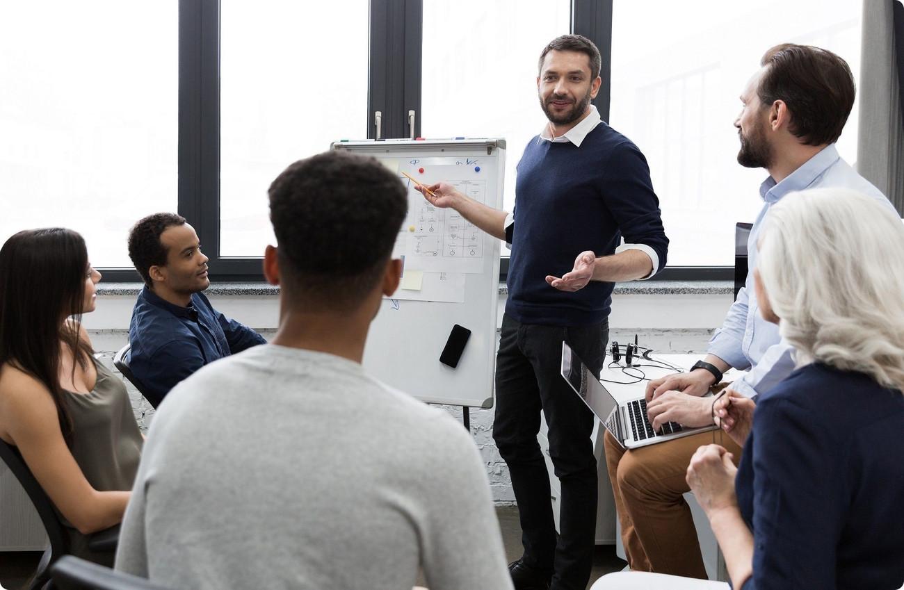Excellence opérationnelle - Réunion autour d'une table de de plusieurs femmes et hommes écoutant un leader dont un de 4 personnes 2 femmes 2 hommes jeunes debout autour d'une table devant un ordinateur