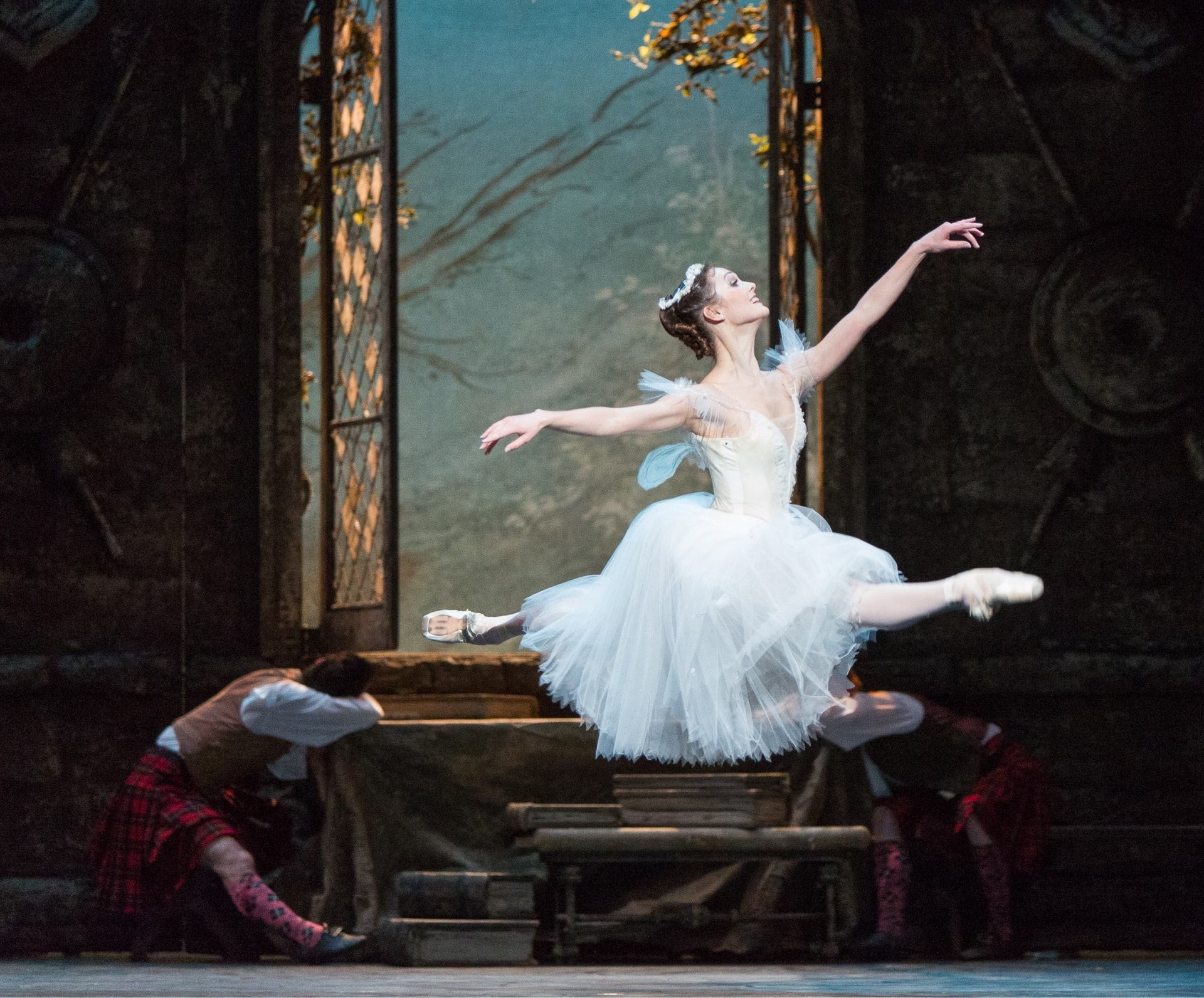 Ballerina in white dress leaps across stage unseen by sleeping dancer below open paned window.