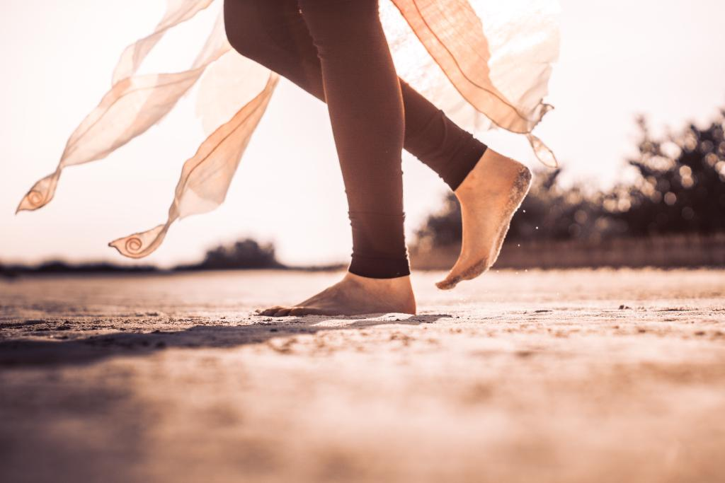 Girl running in the sand in beautiful sunlight