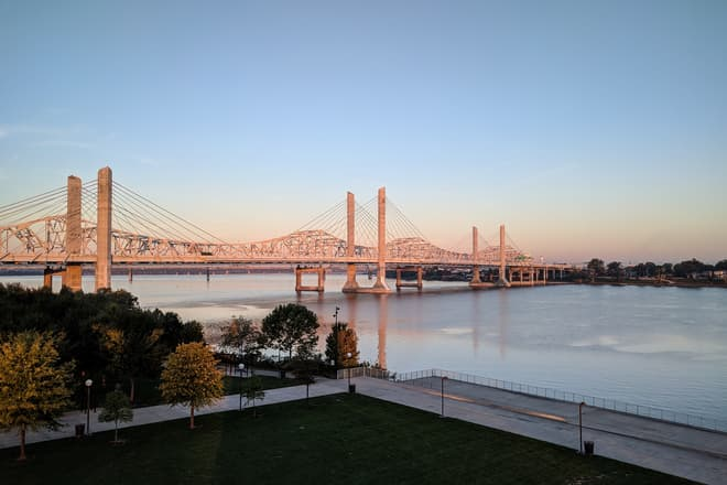 A brutalist suspension bridge made of white steel and concrete pylons crosses the Ohio River between Kentucky and Indiana.