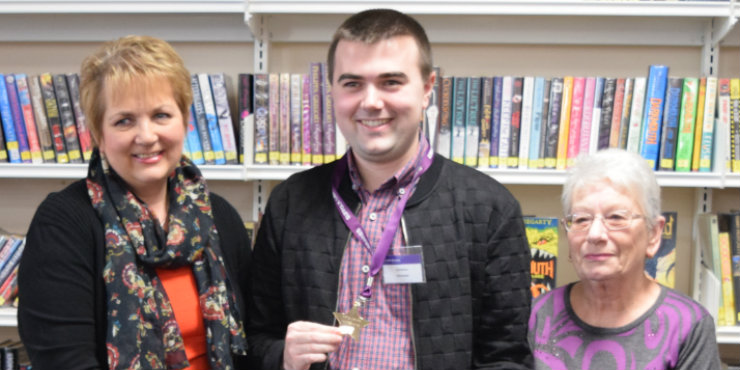 A man with a medal flanked by two women in front of a book shelf