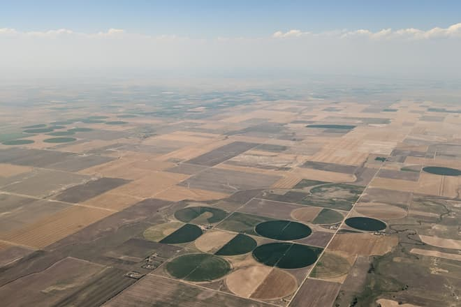 Green and brown farm fields and pastures in eastern Colorado as seen from the air. A tight cluster of circular fields can be seen near the center foreground of the image.