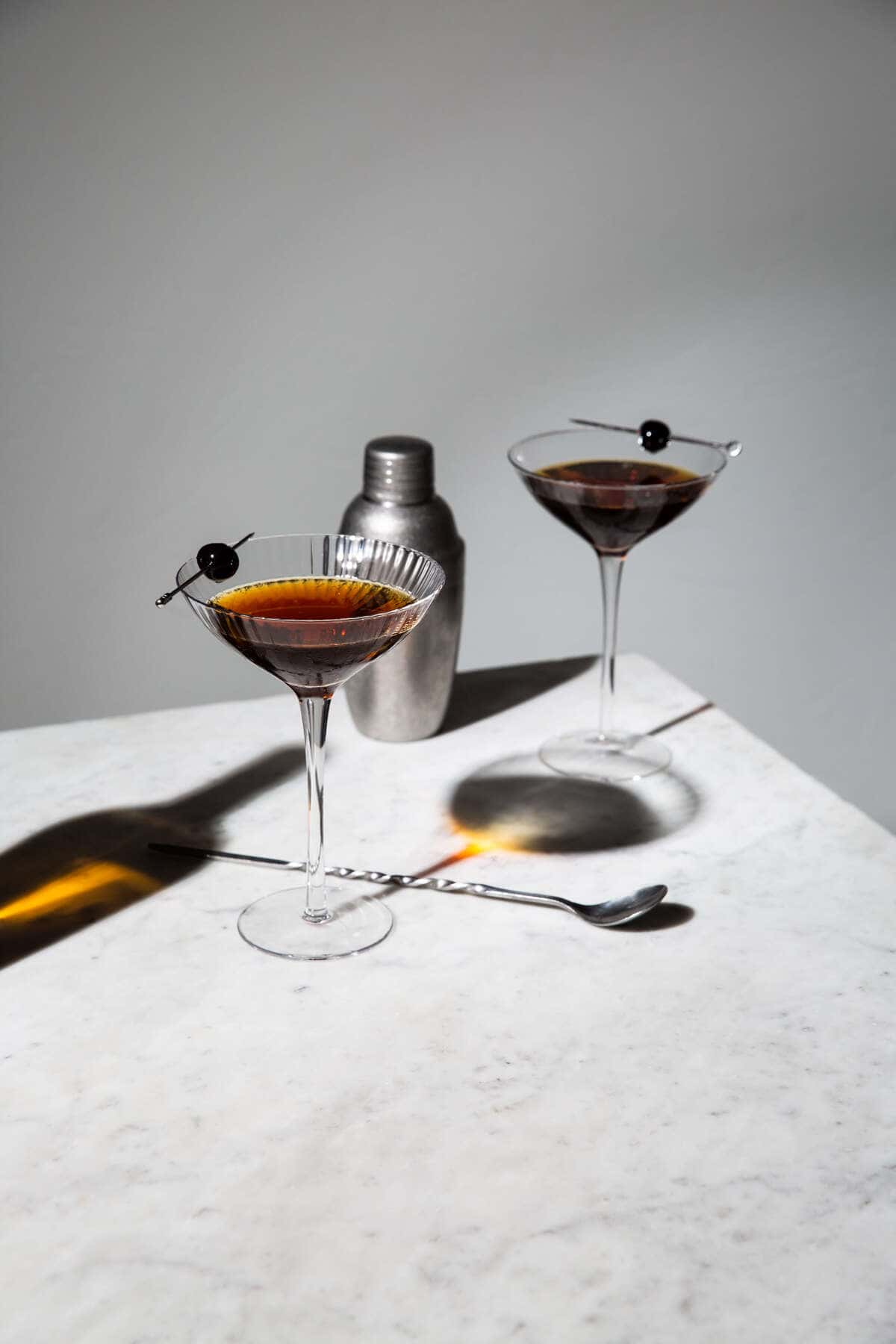 rob roy whisky cocktail in glasses set on marble