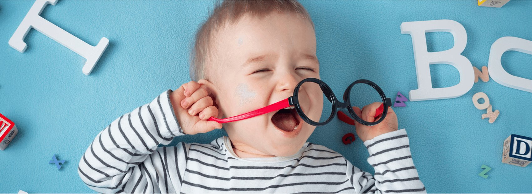 A baby laughing while holding a pair of toy glasses