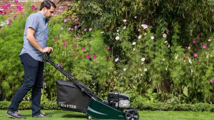Man pushing lawnmower across his lawn