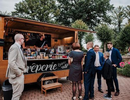 Erwartungsvoll auf Crêpe-Ausgabe wartende, schick gekleidete Hochzeitsgäste vor mobiler Creperie