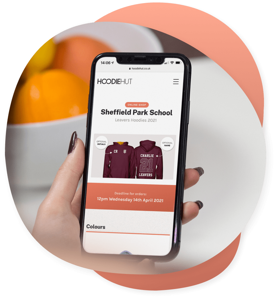 A student holding an iPhone that shows the leavers hoodies online shop page