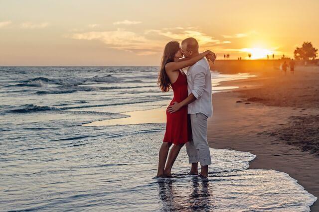 Casal se beixando com os pés na areia na práia