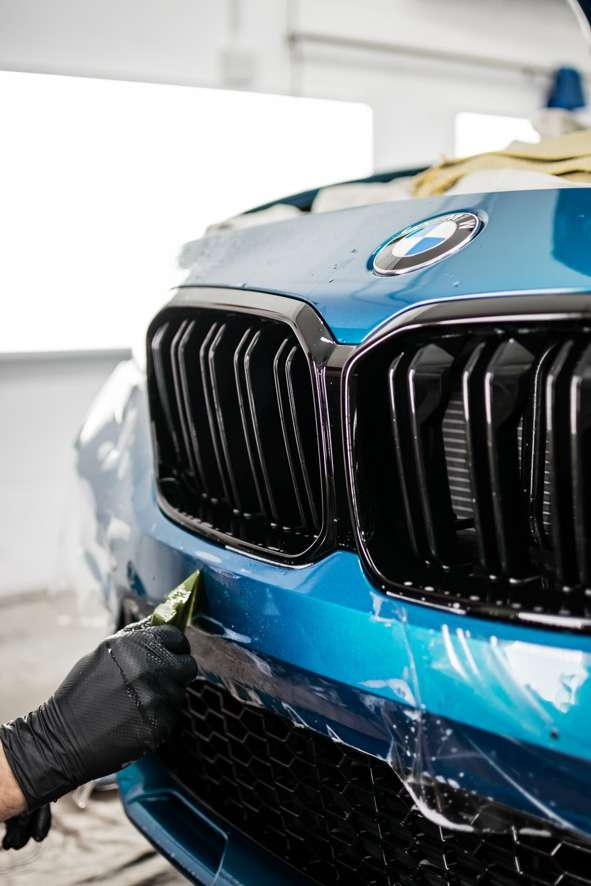 Paint protection film (PPF) being applied to front bumper of blue BMW M2C
