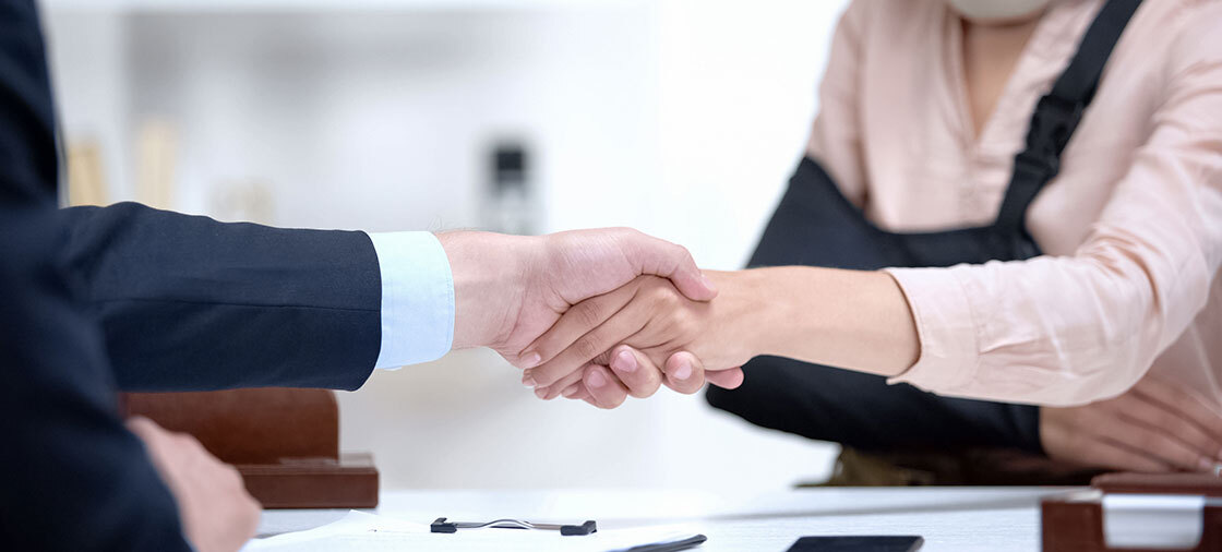 Injured woman shaking hands with an attorney