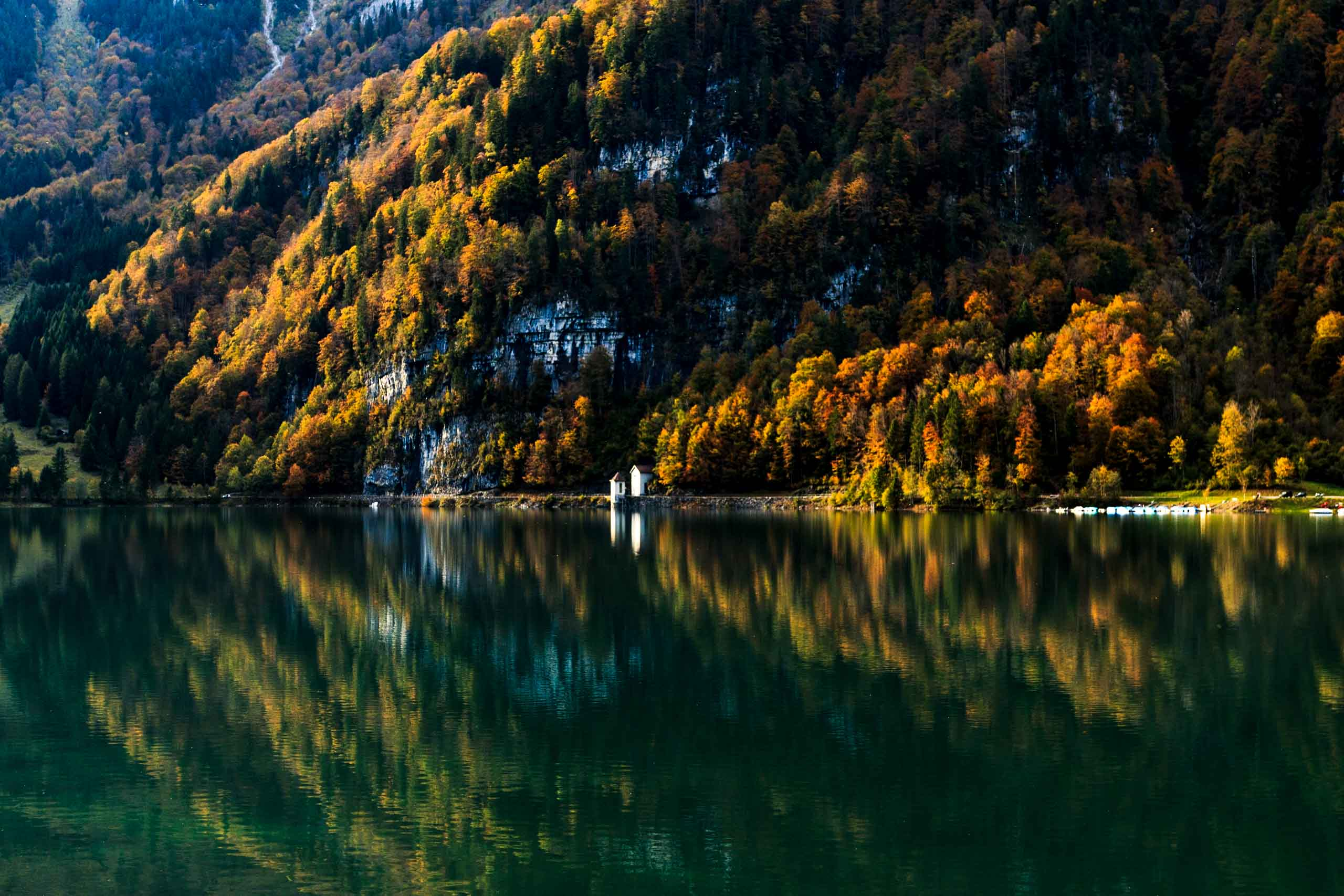 Building with autumn forest in the background. Reflection in lake.