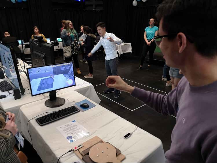 My friend James, stood in front of a student project at the Interactive Media Showcase. James has his arm raised as he tried to use the motion controls to cook a meal as instructed by the game he is playing on screen.
