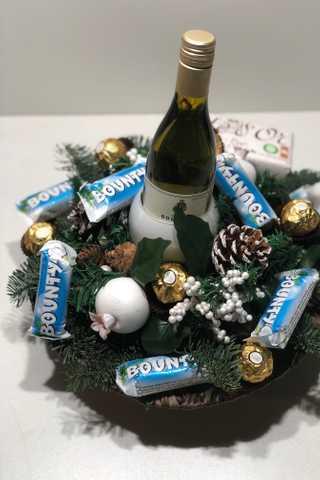 Wit rond kerststuk met fles witte wijn
