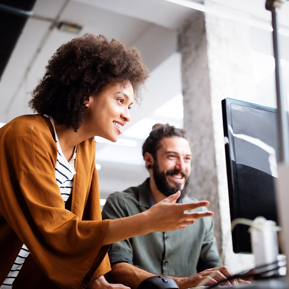 smiling woman showing man computer screen