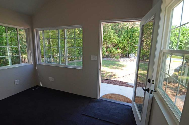 Internal view of a backyard office with light-color painted walls and carpeted floors, from Tuff Shed.