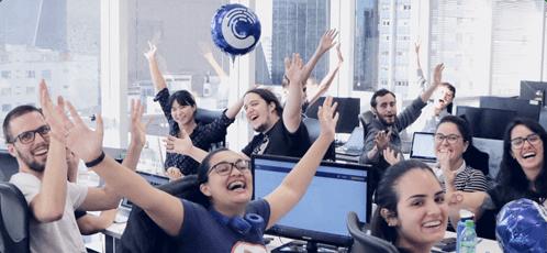 Funcionários da Cobli, sorrindo e com as mãos para cima