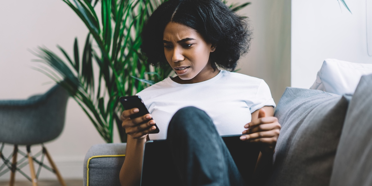 Woman at home, on the couch, trying to complete a task on a mobile app, appearing frustrated.